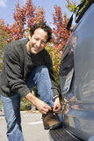 Man leaning against car bumper, tying shoelace, smiling, portrait Royalty Free Stock Photo