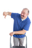 Man Leaning Against a Chair in Thumbs Down Sign Stock Image
