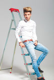 Man leaning against a ladder while posing in studio Stock Photos