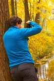 Man leaning against a tree and taking photo of an autumnal fores Royalty Free Stock Photography