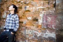 Man leaning against wall Stock Photo