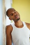 Man leaning against wall with eyes closed Royalty Free Stock Photo