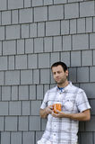 Man leaning against a wall holding a coffee mug. Stock Photos