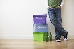 Man Leaning Against Wall By Recycling Containers Royalty Free Stock Photos