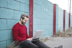 Man Leaning Against Wall Using Laptop Stock Image