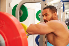 Man leaning on barbells in a rack after weightlifting at gym Stock Images