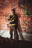 Man leaning on a brick wal Stock Images