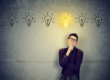 Man leaning on brick wall looking for best solution idea Stock Photo