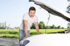 Man leaning on car with opened bonnet. Feeling hopeless. Portrait of young handsome man with beard leaning on car with opened bonnet and looking sad Stock Photo