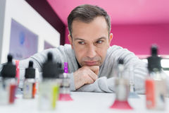 Man leaning on counter contemplating bottles electronic cigarette favours. Man leaning on counter contemplating bottles of electronic cigarette favours Royalty Free Stock Images