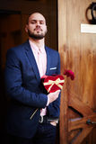 Man leaning on the door waiting for his girlfriend with a flower and gift for her Royalty Free Stock Images