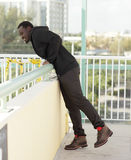 Man leaning over the ledge Stock Images
