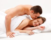Man leaning over smiling woman in bed Royalty Free Stock Images