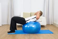 Man leaning on pilates ball doing exercise Stock Photos