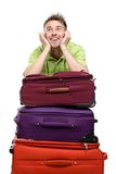 Man leaning on the pile of suitcases. Isolated on white. Concept of journey and cool vacations Royalty Free Stock Images