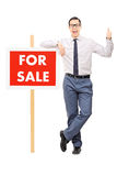 Man leaning on for sale poster and giving thumb up Royalty Free Stock Images
