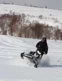 Man Leaning the snowmobile right over in the backcountry Stock Images