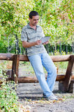 Man leaning on a timber fence with a tablet Stock Images