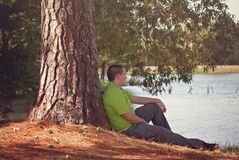 Man leaning on tree royalty free stock image