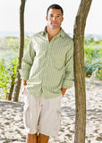 Man leaning on tree at beach. Man leaning on tree at the beach Stock Photos