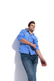 Man leaning on a wall while fixing his sleeve. Royalty Free Stock Images