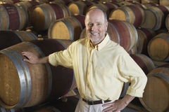 Man Leaning On Wine Cask In Cellar. Portrait of happy middle aged man leaning on wine cask in cellar royalty free stock image