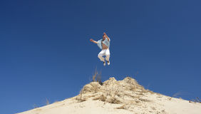 Man Leaping on Hilltop. Man leaping upwards off white sandy hill, blue sky Royalty Free Stock Photos