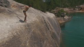 Man leaping on the rocks near lakeshore and jumping off cliff into the water. Summer fun lifestyle stock video footage