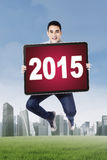 Man leaps on the field with number 2015. Young asian man jumping on the meadow while holding a board with number 2015 Royalty Free Stock Photo