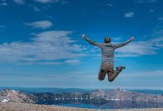 Man Leaps at Overlook to Crater Lake Royalty Free Stock Images