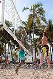 Man Leaps To Spike Ball In Miami Beach Volleyball Game. Miami, FL, USA - December 27, 2014:  A man jumps high to spike the ball in a pickup game of beach Royalty Free Stock Image