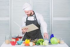 Man learn recipe. Improve cooking skill. Book family recipes. Ultimate cooking guide for beginners. According to recipe. Man bearded chef cooking food. Guy royalty free stock image