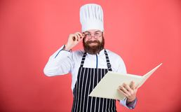 Man learn recipe. Try something new. Cookery on my mind. Improve cooking skill. Book recipes. According to recipe. Man. Bearded chef cooking food. Culinary arts royalty free stock images