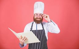 Man learn recipe. Try something new. Cookery on my mind. Improve cooking skill. Book recipes. According to recipe. Man. Bearded chef cooking food. Culinary arts royalty free stock photography
