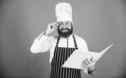 Man learn recipe. Try something new. Cookery on my mind. Improve cooking skill. Book recipes. According to recipe. Man. Bearded chef cooking food. Culinary arts stock photos