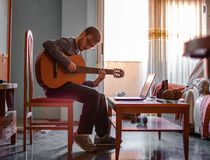 Man learning to play the guitar stock photos