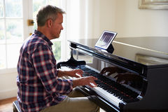 Man Learning To Play Piano Using Digital Tablet Application Stock Image
