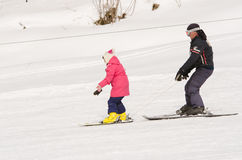 A man learns to ski teenage girl on a snow-covered slope ski resort Dombai Royalty Free Stock Photography