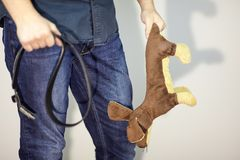 The man with leather belt in one hand and the children toy dog in the other one. The concept of home violence, cruelty. Indoors, copy space royalty free stock photo