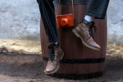 Man with leather boots sitting on wooden barrel and holding vintage film camera in a leather case royalty free stock photo