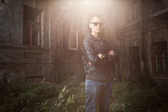 Man in leather coat posing against grungy building in sun rays Royalty Free Stock Photography