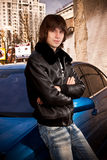 Man in leather coat posing near blue car Stock Photo