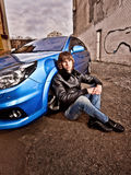 Man in leather coat sitting leaning to front wheel of blue car Royalty Free Stock Photography