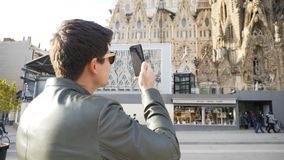 Spain - Barcelona, 12 August 2018: Man in leather jacket and black sun glasses taking photo of the gothic cathedral. Man in leather jacket and black sun glasses stock image