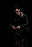 Man in leather jacket and boots wearing sunglasses sitting Royalty Free Stock Images