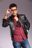 Man in leather jacket holding his glasses Stock Images