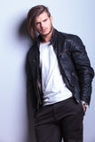 Man in leather jacket leaning against a gray wall Stock Photo