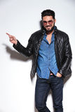 Man in leather jacket pointing  finger to his side Stock Photography