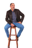 Man in leather jacket posing seated on stool Stock Image