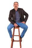 Man in leather jacket posing on stool with legs open Royalty Free Stock Images